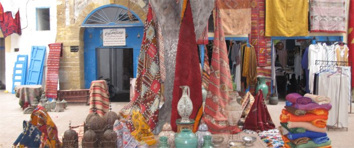 Shopkeeper displays his wares throught a square in the Essaouira Medina